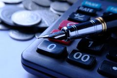 Fountain pen and Money coins stack and calculator for finance concept Stock Images