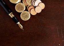 Fountain pen and Money coins stack on wooden table for finance c royalty free stock images