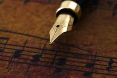 Fountain pen on music sheet stock photo