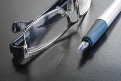 Fountain pen next to a pair of reading glasses stock images