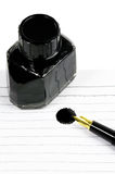 Fountain pen and notebook. Classic black fountain pen on open notebook with ink bottle with stain on page Stock Image