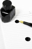 Fountain pen and notebook. Classic black fountain pen on open notebook with ink bottle with stain on page Stock Photography