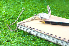 Fountain pen and pocketwatch on book Royalty Free Stock Photo