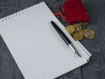 Fountain pen, red money bag and notebook on a wooden table. The concept of the accounting of funds Royalty Free Stock Image