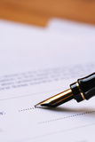 Fountain Pen Signing Document. A classic gold-nibbed fountain pen, poised over signature line of document stock image