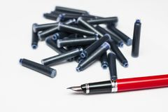 Fountain pen and spare ink cartridges. Fountain pen with burgundy cherry color on the barrel and black grip section. Uncovered metallic nib. Lots of ink Stock Photo