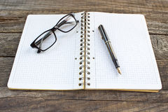 Fountain pen and spiral notebook with eyeglasses Stock Photos