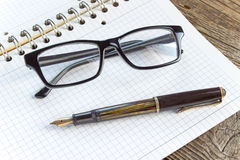 Fountain pen and spiral notebook with eyeglasses Stock Image