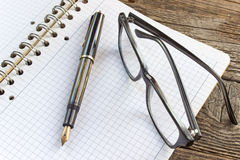 Fountain pen and spiral notebook with eyeglasses Stock Photo