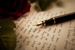Fountain pen on text sheet paper with rose royalty free stock images