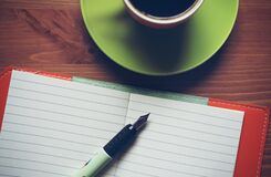 Fountain Pen on Top of Notebook Beside Drinking Mug Stock Photos