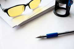 Fountain pen on white background glasses and stamp on print next to white paper. Office work Royalty Free Stock Images