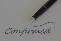 Fountain pen on white paper - CONFIRMED. Close up view of black fountain pen on white paper with business message - CONFIRMED royalty free stock photos