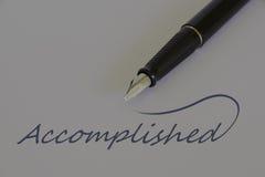 Fountain pen on white paper, message - ACCOMPLISHED. Close up view of black fountain pen on white paper with business message - ACCOMPLISHED royalty free stock photo