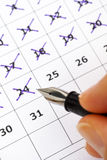 Fountain pen in woman hand marking days on calendar Royalty Free Stock Photo