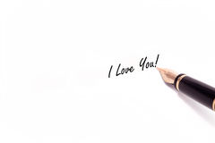 Fountain Pen Writing. A photo of a fountain pen writing I Love You in black ink. The pen and ink are isolated on a white background Royalty Free Stock Images