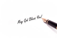 Fountain Pen Writing. A photo of a fountain pen writing May God Bless You in black ink. The pen and ink are isolated on a white background Stock Photos