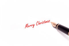 Fountain Pen Writing. A photo of a fountain pen writing Merry Christmas in red ink. The pen and ink are isolated on a white background Royalty Free Stock Image