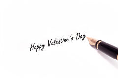 Fountain Pen Writing. A photo of a fountain pen writing Happy Valentine's Day in black ink. The pen and ink are isolated on a white background Royalty Free Stock Images
