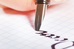 Fountain pen writing the word Dear on graph pad Stock Photos