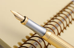 Fountain pen on a yellow notebook Royalty Free Stock Photo