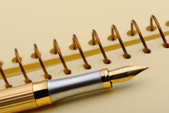 Fountain pen on a yellow notebook Royalty Free Stock Photography