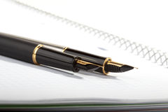Fountain pens lays on a writing-book Stock Image