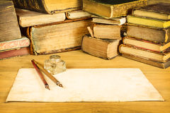 Fountain pens with paper in front of old books Royalty Free Stock Image
