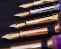 Fountain Pens. Fountain Pen nibs in a row on a black cloth short depth of field Royalty Free Stock Photos