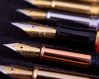 Fountain Pens. In a row on a black cloth Stock Photos