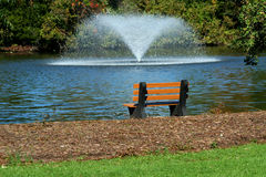 Fountain on a pond with park bench Stock Photography
