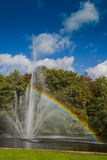 A fountain in a pond, with a rainbow. A fountain, with multiple fountainheads, bathed in mid day bright light, making a beautifull rainbow Stock Photo