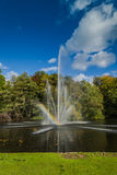 A fountain in a pond, with a rainbow Royalty Free Stock Images
