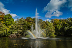 A fountain in a pond, with a rainbow. A fountain, with multiple fountainheads, bathed in mid day bright light, making a beautifull rainbow Royalty Free Stock Images