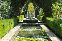 Fountain and pool in the Generalife, Granada. Water games and beautiful vegetation in the gardens of the Generalife on the hill of the Alhambra in Granada, Spain stock image