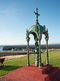 Fountain at Portmahamock. Elaborate fountain at Portmahock on the north east coast of Scotland overlooking the harbour with fishing boats tied up Stock Photo