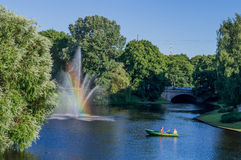 The fountain with a rainbow and background. In a sunny day Stock Photos