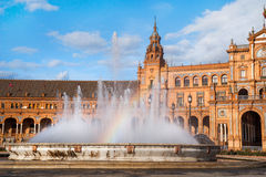 Fountain with rainbow on Plaza de Espana in Sevillle. Fountain with rainbow and part of architectural complex on Plaza de Espana in Sevillle Stock Image