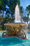 Fountain in Rimini Italy. A fountain in Rimini Italy on a sunny day in January featuring horses. The fountain is in a square, and surrounded by trees stock photo