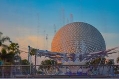 Fountain and Spaceship Earth attraction in Epcot on light blue sky background at Walt Disney World .
