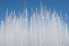 Fountain splashes waterdrops. Fountain jet on blue sky background Stock Image
