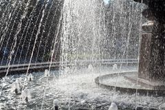 Fountain with spray in the Park in the autumn bright Sunny day where people walk enjoy a beautiful waterfall royalty free stock photography