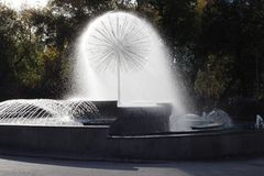 Fountain with splashes in the Park in autumn bright Sunny day stock photo