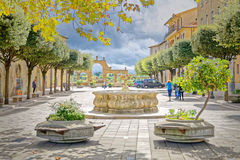 The fountain in the square of Pitigliano illuminated by a ray of sunshine on a stormy day Stock Images