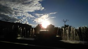 Fountain in the square in the rays of the setting sun Stock Image