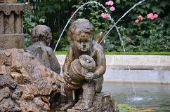 Fountain statue of little boy. Fountain with a little boy statue, roses on background Stock Photo