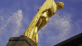 Fountain with statue slow motion. Fountain with golden statue in Peterhof slow motion with sky on the back stock video