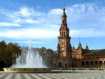The fountain and the stunning tower of Plaza de Espana under cloudy blue sky, Seville Stock Images