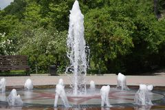 Fountain, summer landscape. Fountain and playground for rest. Jet from under the ground Royalty Free Stock Image
