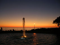 Fountain at sunset. Looking at the water play fountain of Barcola at sunset Royalty Free Stock Image